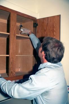 Ponga los cebos de cucaracha alrededor de los bordes de los armarios de la cocina y en los rincones. Este profesional aplica el cebo de gel.